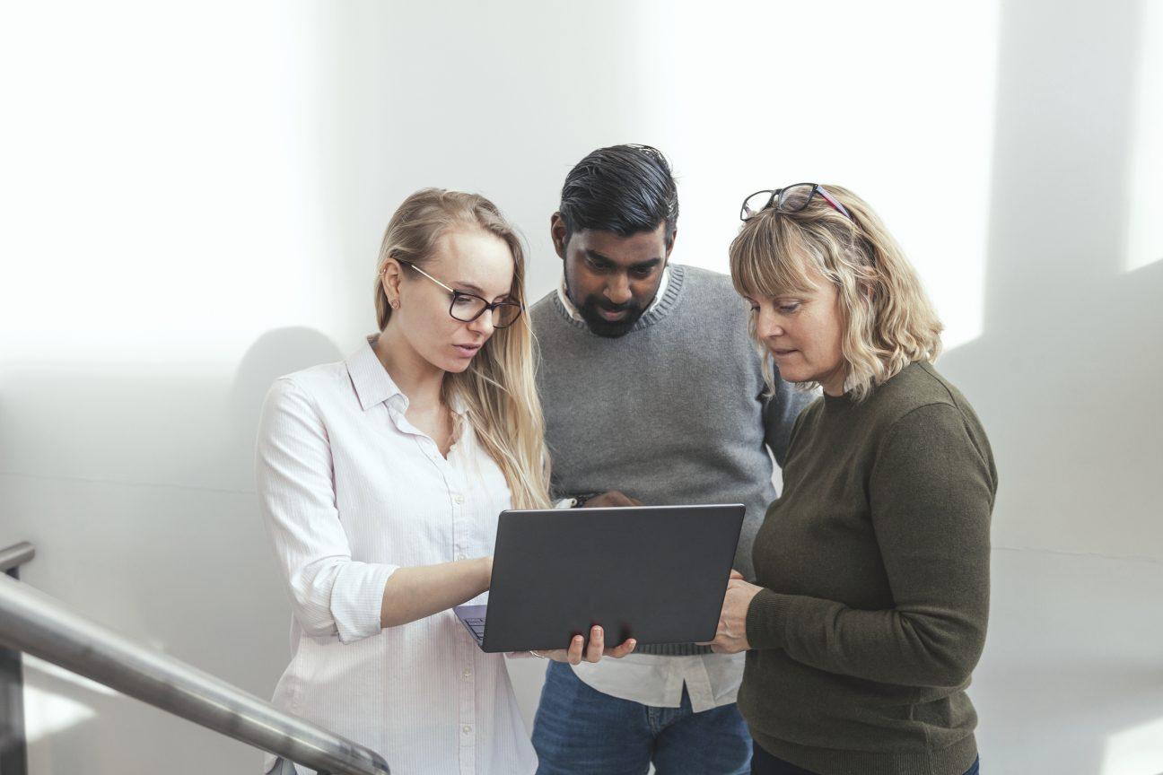 Tre arbetskollegor står i trapphus och diskuterar något på en dator.  Foto: Bildbyrån Scandinav